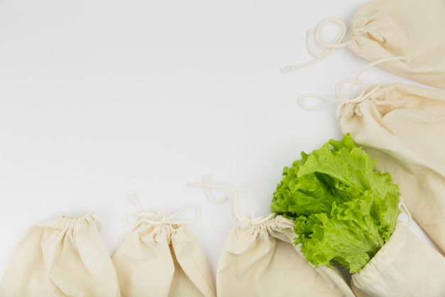 Flache lage von wiederverwendbaren beuteln mit salat