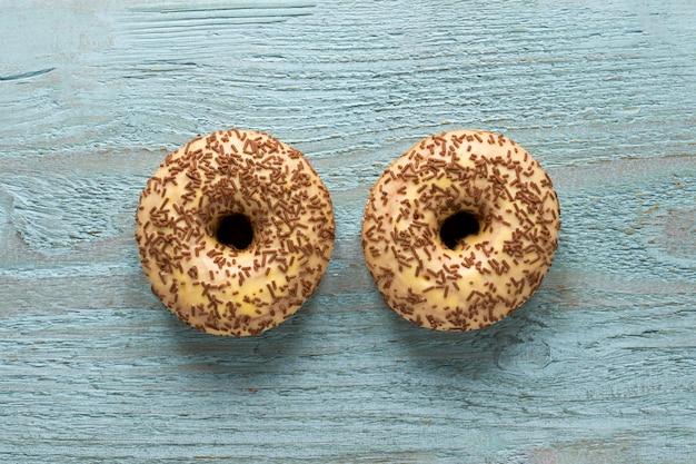 Flache lage von zwei donuts auf holzoberfläche