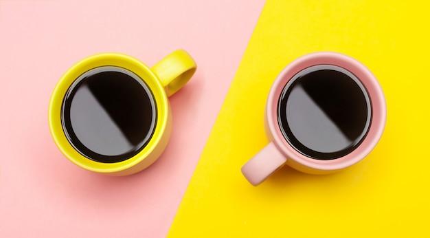 Flache lage von zwei kaffeetassen mit rosa und gelb