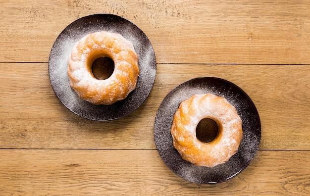 Flache lage von zwei tellern mit donuts