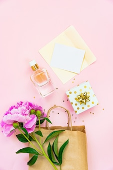Flache lage weiblicher kosmetikprodukte, geschenkbox und leere karte auf rosafarbenem hintergrund. platz kopieren.