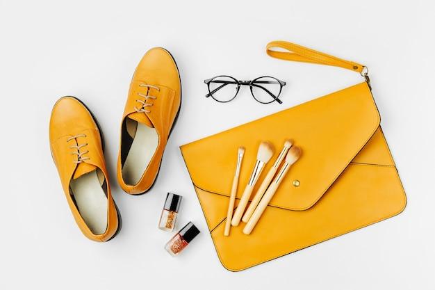 Flache lage weiblicher modeaccessoires schuhe make-up-produkte und handtasche auf orangen farben