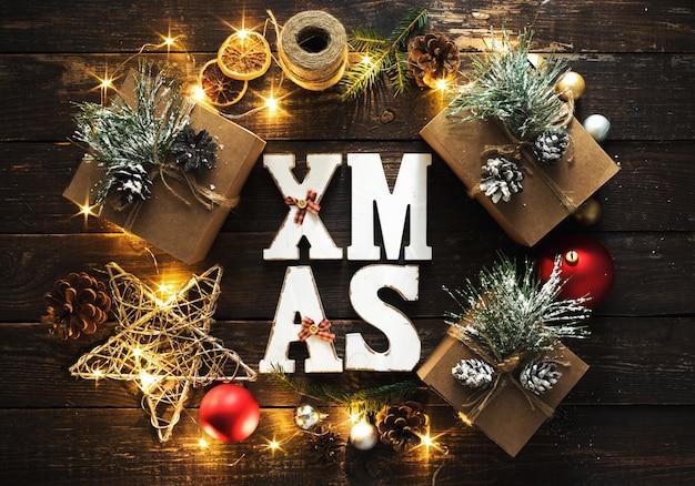 Flache lage weihnachtswort-weihnachtskranzdekoration beleuchtet hölzerne draufsicht