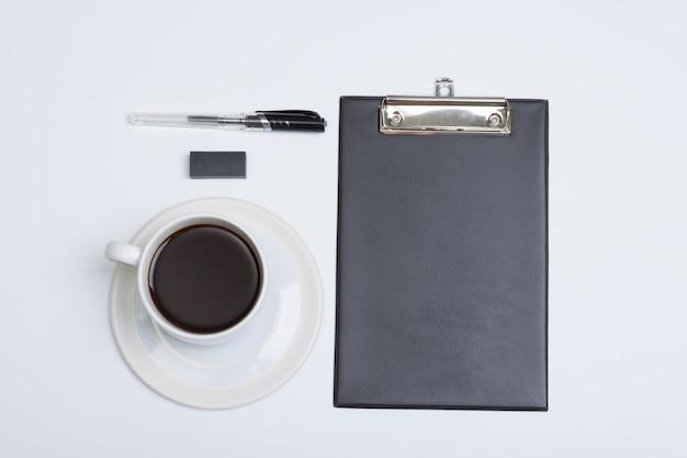 Flache lage, weißer tabellenschreibtisch des modernen büros der draufsicht. notizblockkaffee, -stift und -gummi auf weiß
