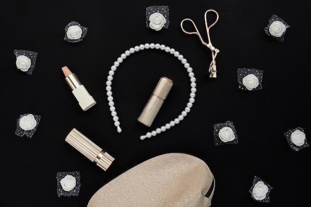 Flache lageanordnung mit kosmetischen produkten auf schwarzem hintergrund