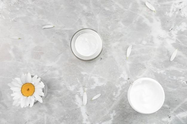 Flache lageansicht der natürlichen creme auf marmorhintergrund
