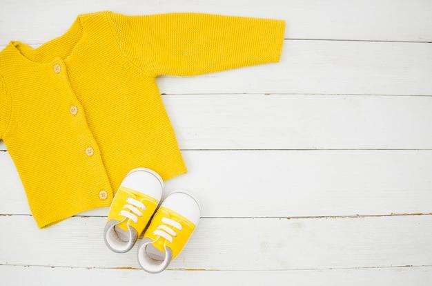 Flache lagebabykleidung mit hölzernem hintergrund