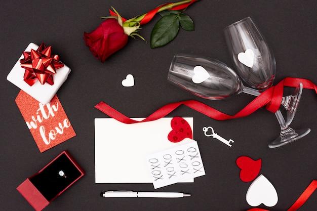 Flache lagedekoration mit gläsern und geschenk auf schwarzem hintergrund