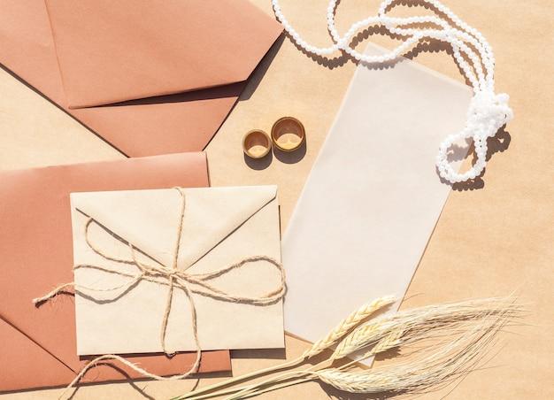 Flache lagehochzeitseinladungen in den umschlägen mit papierhintergrund