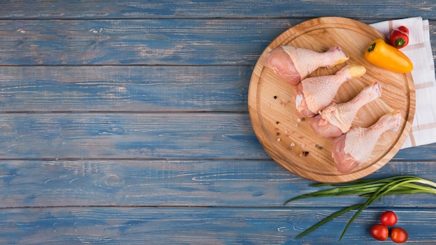 Flache lagehühnertrommelstöcke auf hölzernem brett und pfeffern mit kopienraum