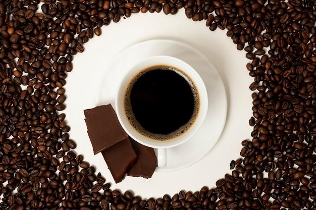 Flache lagekaffeetasse auf bohnenhintergrund