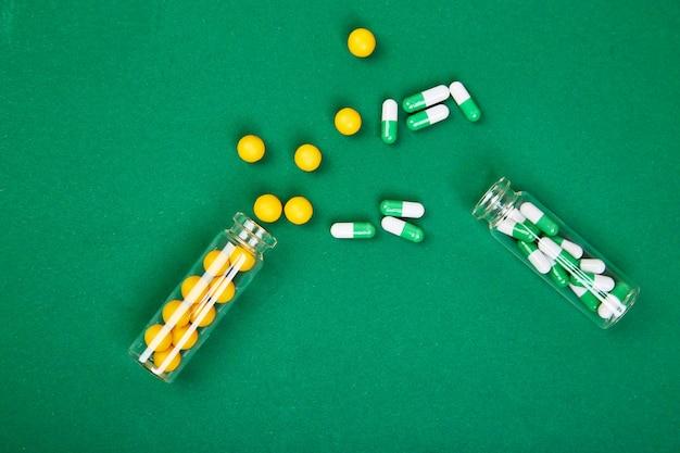 Flache lageunkosten von gelben und grünen pillen im glasgefäß auf papierhintergrund
