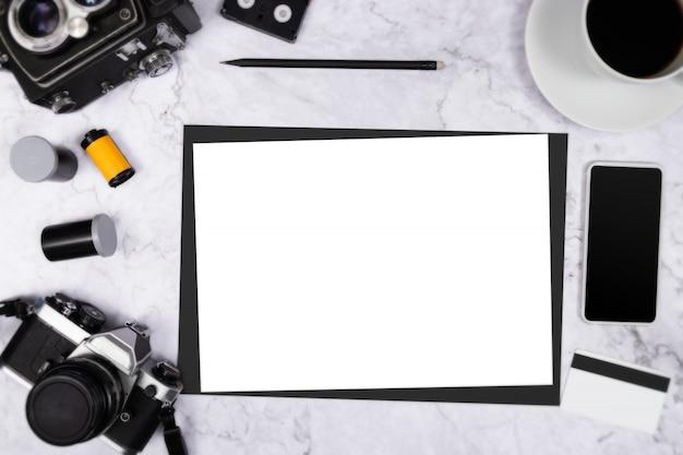 Flache lageweinlesekamera auf weißem marmorhintergrund mit weißem leerem papier copyspace