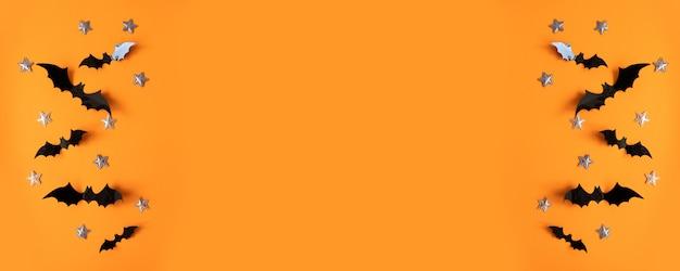 Flache lagezusammensetzung halloweens von schwarzen papierschlägern fliegen oben und goldsterne auf orange oberfläche