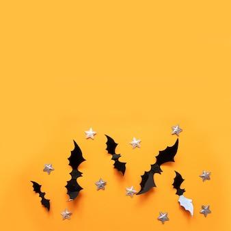 Flache lagezusammensetzung halloweens von schwarzen papierschlägern fliegen oben und goldsterne