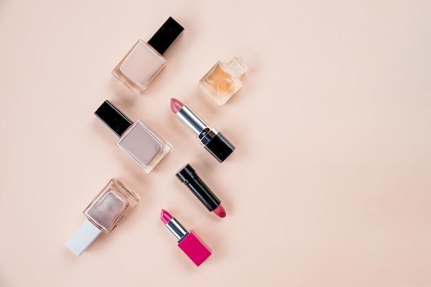 Flache lagezusammensetzung mit dekorativer kosmetik auf pastellhintergrund schönheitskonzept. top view.professional make-up. flasche parfüm und kosmetische produkte lokalisiert