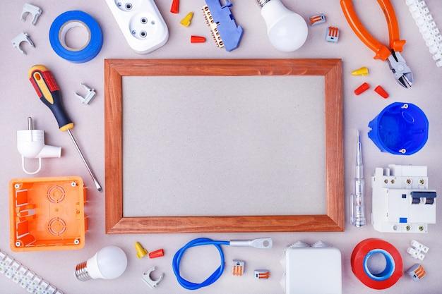 Flache lagezusammensetzung mit elektriker `s werkzeugen, ausrüstung und raum für text auf grauer oberfläche. hauptreparaturkonzept.