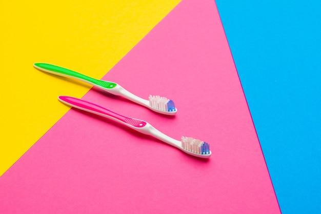 Flache lagezusammensetzung mit manuellen zahnbürsten auf farbhintergrund, abschluss oben