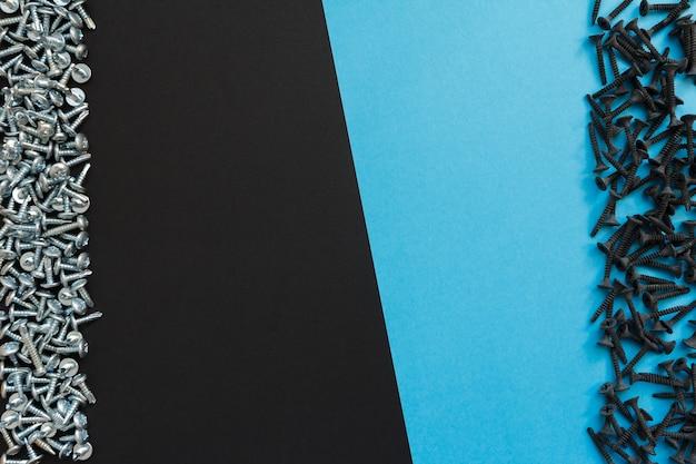 Flache lagezusammensetzung mit verschiedenen schrauben auf schwarzem und blauem hintergrund. draufsicht auf das checklistenkonzept