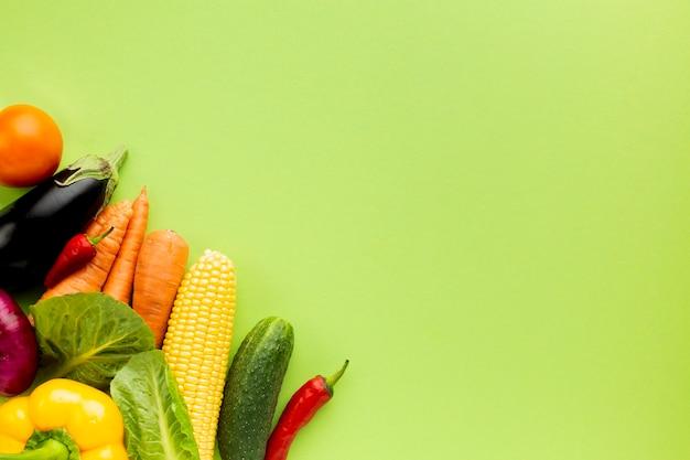 Flache lagezusammenstellung von veggies auf grünem hintergrund mit kopienraum