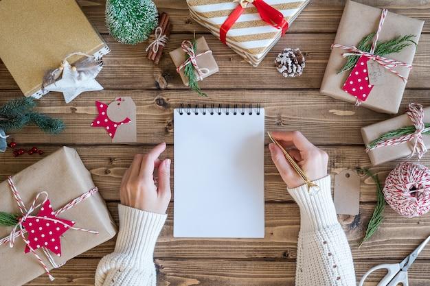 Flache laie der frauenhände, die auf notizbuch mit weihnachtsgeschenk schreiben.