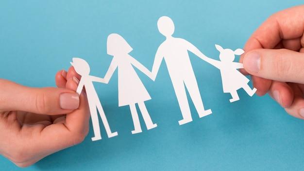 Flache laien, die in händen niedliche papierfamilie halten