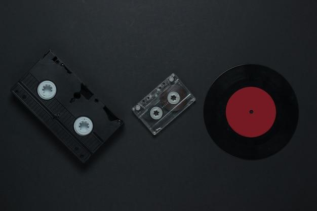 Flache laien retro-medien und unterhaltung. schallplatte, audiokassette, vhs auf schwarzem hintergrund. 80er jahre. draufsicht