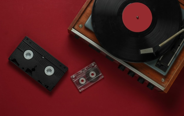 Flache laien retro-medien und unterhaltung. schallplattenspieler mit schallplatte, audiokassette, vhs auf rotem hintergrund. 80er jahre. draufsicht