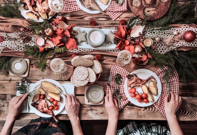 Flache laien von freunden, die zusammen essen und trinken. draufsicht der leute, die partei haben, versammeln, zusammen am rustikalen hölzernen tisch feiern