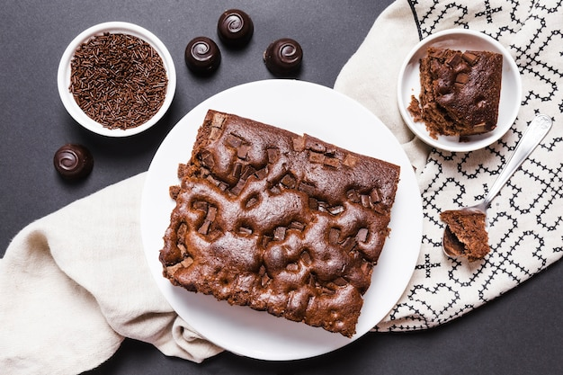 Flache laienanordnung mit schokoladenkuchen und süßigkeiten