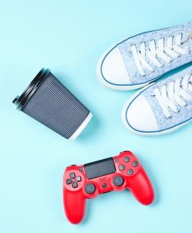 Flache laienart-jugend-hipster-accessoires auf pastellblauem hintergrund. rotes gamepad, turnschuhe, kaffeetasse aus papier