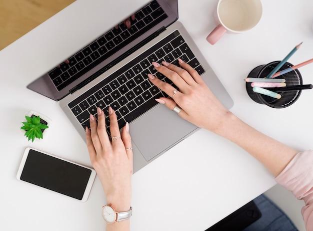 Flache laienfrau, die am laptop arbeitet