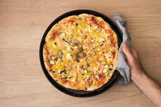 Flache laienhand, die pfanne mit gekochter pizza hält