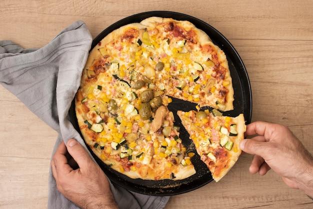 Flache laienhand, die pizzascheibe von der wanne mit pizza nimmt