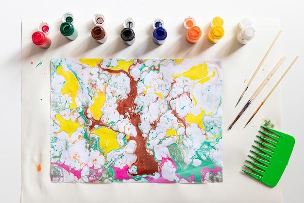 Flache laienkomposition mit abstrakter ebru-zeichnung und werkzeugen