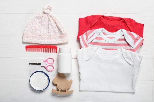 Flache laienkomposition mit babykleidung und zubehör auf hölzernem hintergrund