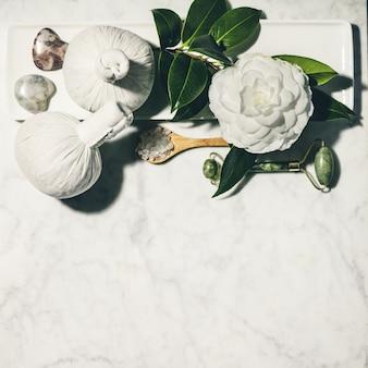 Flache laienkomposition mit frühlingskamelienblume und verschiedenen schönheitspflegeprodukten auf weißem marmortisch