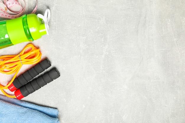 Flache laienkomposition mit gesundem lebensstilzubehör auf grauem hintergrund