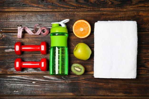 Flache laienkomposition mit gesundem lebensstilzubehör auf hölzernem hintergrund