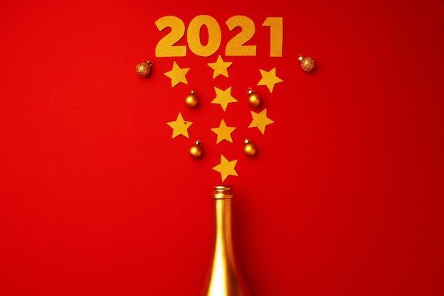 Flache laienkomposition mit goldener champagnerflasche und weihnachtskugeln draufsicht