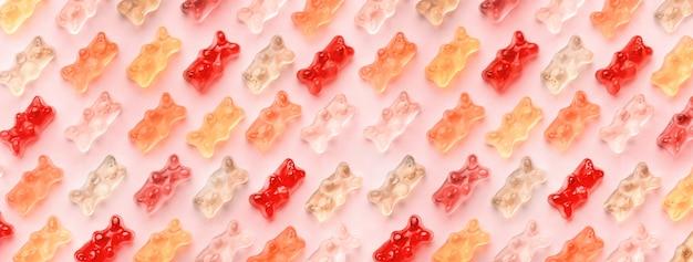 Flache laienkomposition mit köstlichen gummibärchen, geleebärenmuster auf rosa