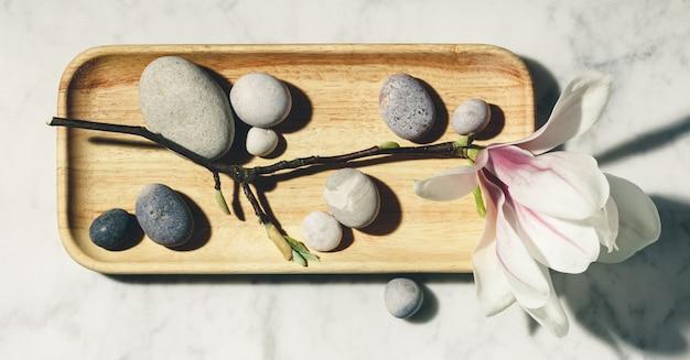 Flache laienkomposition mit schönen frühlingsmagnolienblumen und grauen steinen auf weißem marmorhintergrund. entspannung und zen-ähnliches konzept.