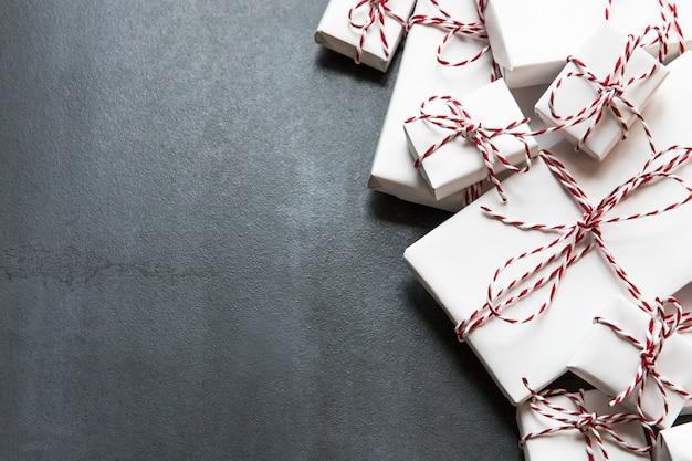 Flache laienkomposition mit weihnachtsgeschenkboxen mit rotem band auf schwarzem hintergrund, kopienraum. winterferienmuster.