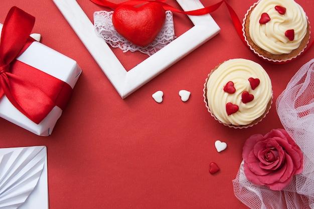 Flache laienkomposition zum valentinstag. geschenk auf einer roten fläche.