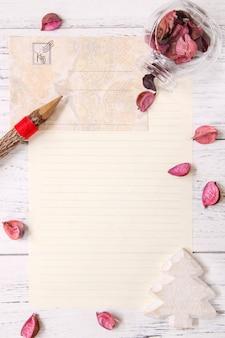 Flache laienlager fotografie lila blütenblätter briefumschlag papier glasflasche holzstift weihnachtsbaum handwerk dekoration
