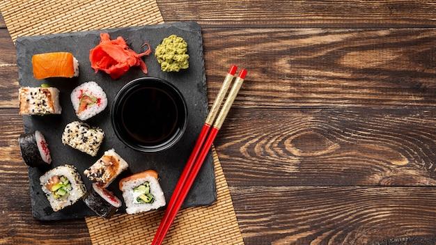 Flache laienmischung von maki sushirollen und essstäbchen mit kopienraum