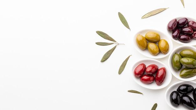 Flache laienmischung von schwarzen roten grünen purpurroten gelben oliven und von öl mit kopienraum