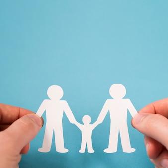 Flache laienperson, die in händen niedliche papierfamilie hält