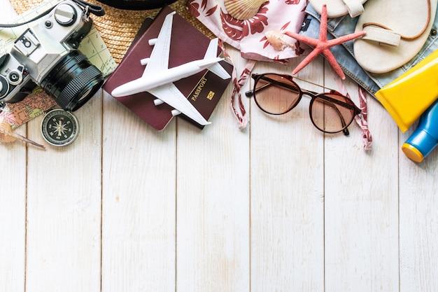Flache laienreisende accessoires auf weißem holztisch. draufsicht reise- oder urlaubskonzept.