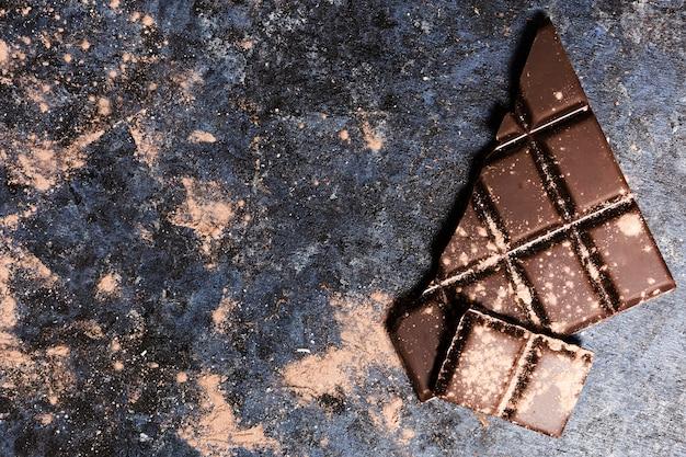 Flache laienschokolade bedeckt im kakao auf schmutztabelle